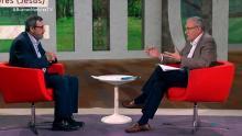El presentador y el invitado charlan sentados en el estudio